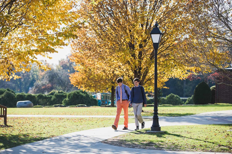 two boys walking down campus path